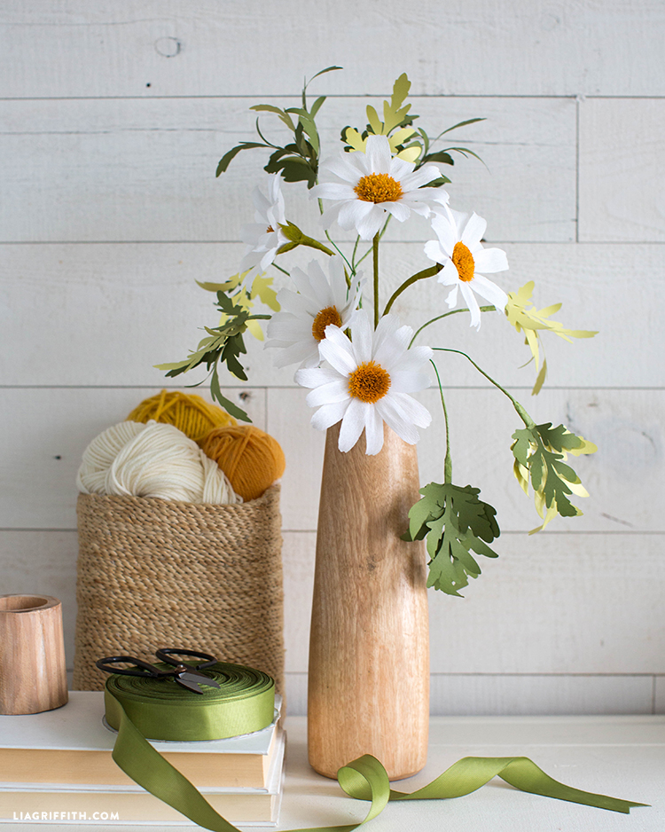 crepe paper daisies in wood vase next to ribbon, books, scissors, and yarn