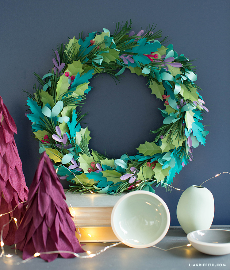 Paper holiday wreath next to mini paper trees on table