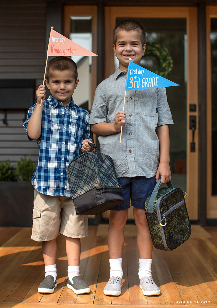 Boys holding backpacks and first day of school DIY pennant flags