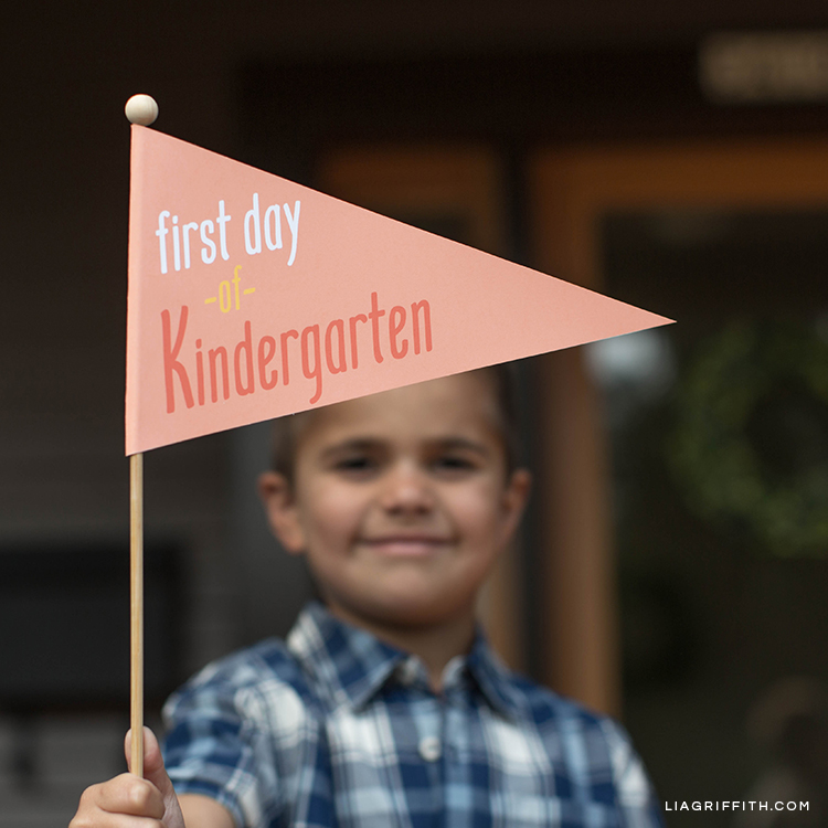 Boy holding first day of kindergarten pennant flag