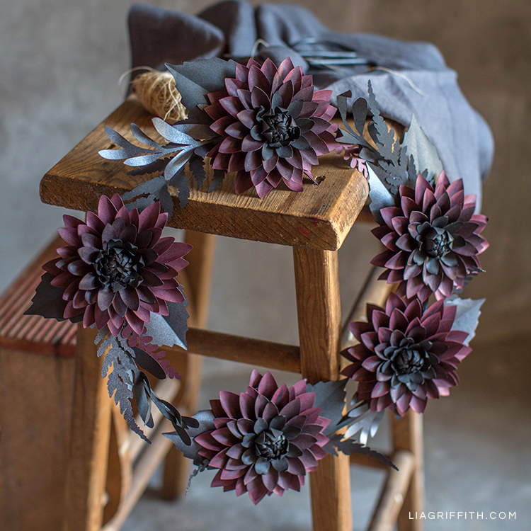 Black and purple paper dahlia wreath hanging on wood stool