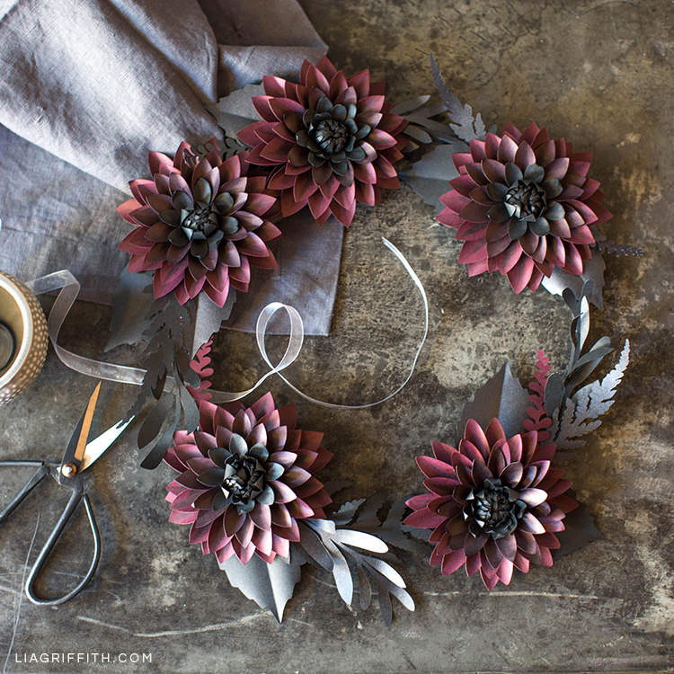 Black and purple paper dahlia wreath next to scissors, ribbon, and cloth