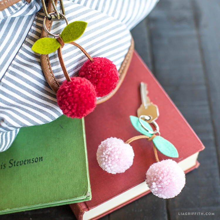 Red cherry pom-pom keychain on backpack and pink cherry pom-pom keychain with key on ring