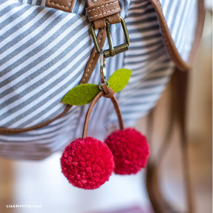 Close-up of red cherry pom-pom keychain on backpack