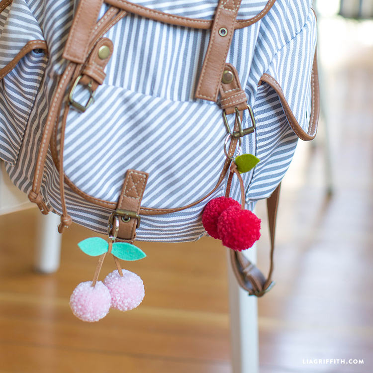 Close-up of pink and red cherry pom-pom keychains on backpack