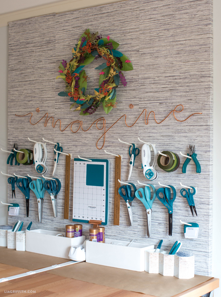 "DIY pegboard with hanging craft tools, ""imagine"" copper wire wall art, and handmade wreath"