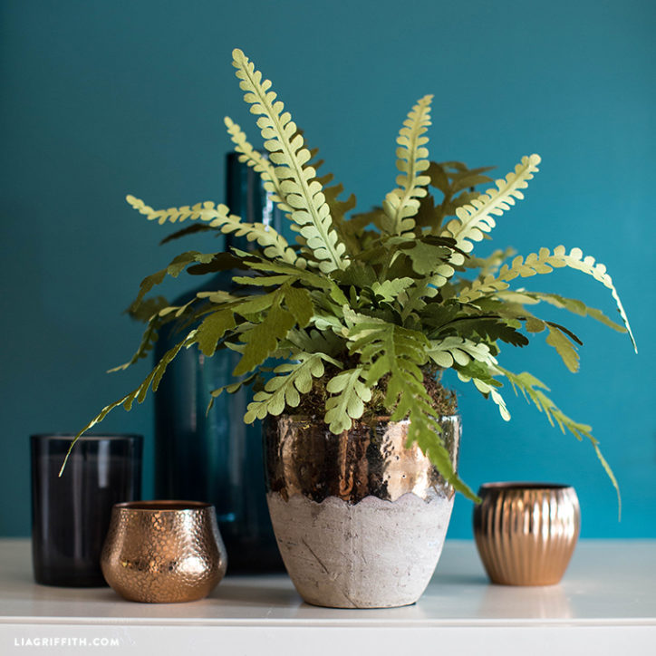 Double-sided crepe paper fern plant in pot next to two small empty pots