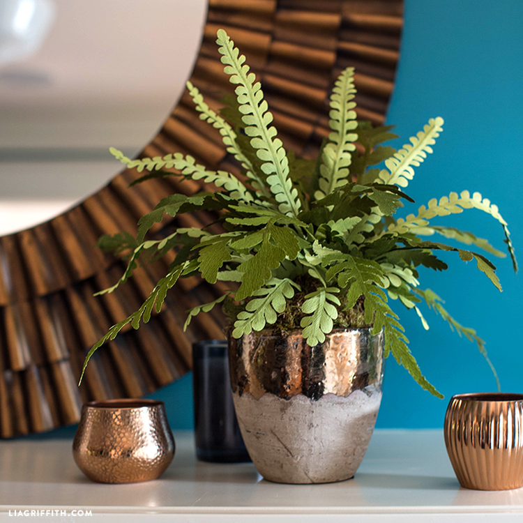 Double-sided crepe paper fern in pot with two small gold pots and wall mirror