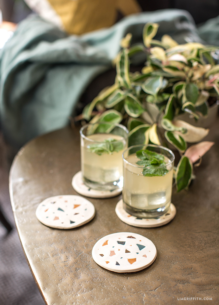 Drinks on faux terrazzo coasters on table next to plant