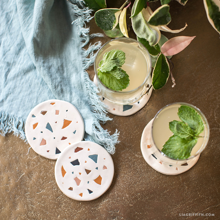 Drinks on faux terrazzo coasters next to linen throw blanket