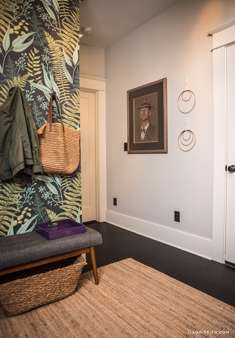 Removable fern wallpaper, wall hooks, mid-century bench, storage basket, wall art, and copper macrame wall art in entryway