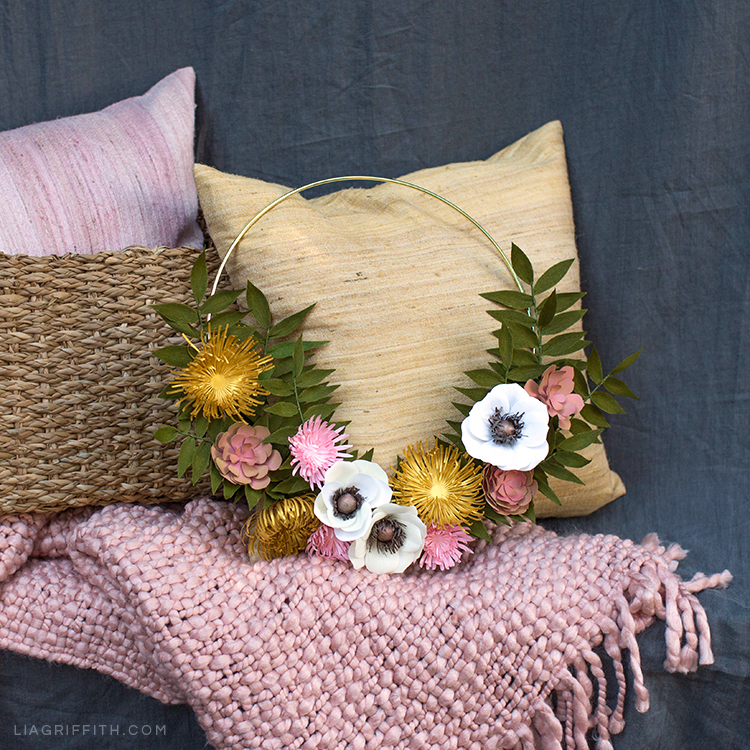 Paper flower wreath for fall with mums, anemones, succulents, and greenery on couch with pink blanket and pink and yellow pillows