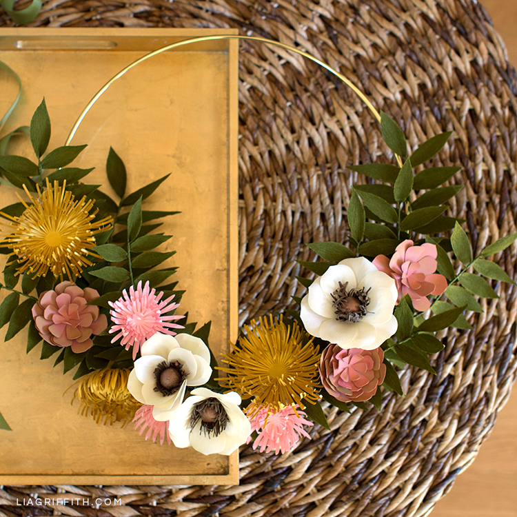 Paper flower wreath for fall with mums, anemones, succulents, and greenery on gold tray on wicker table