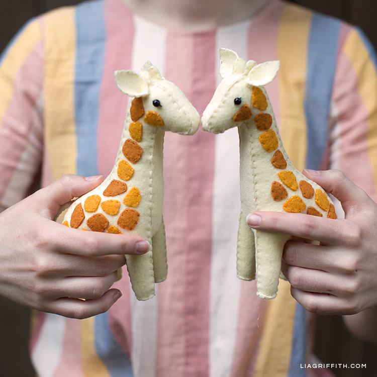 Designer holding handsewn felt giraffes