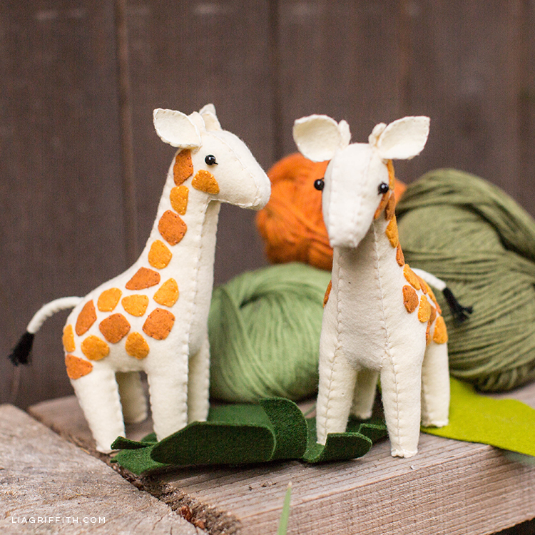 Handsewn felt giraffes next to yarn