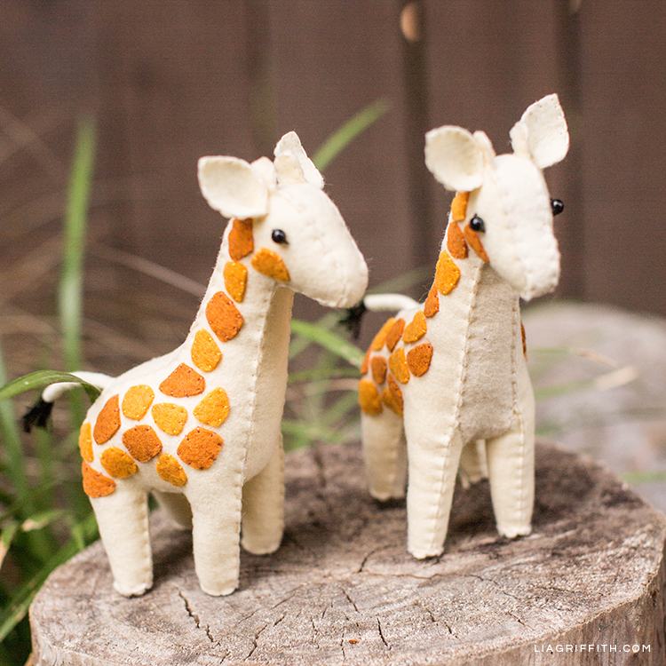 Handsewn felt giraffes on tree stump