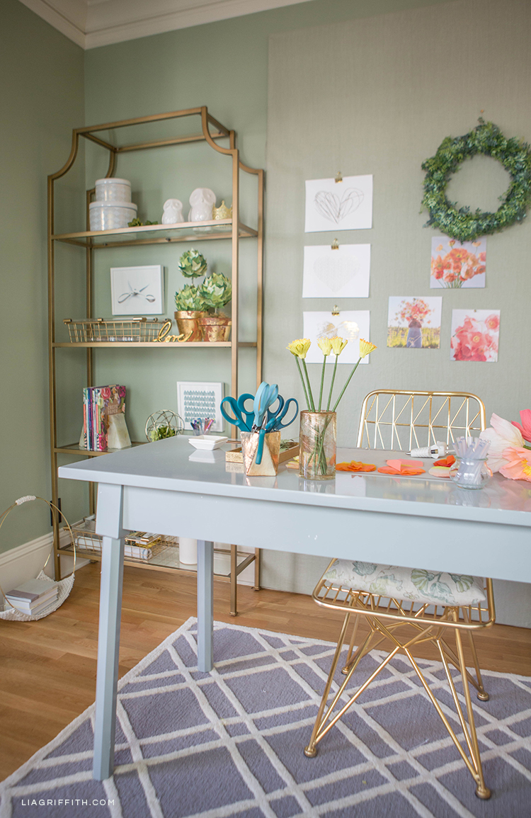 Creative workspace with grey chair, gold desk, and gold etagere from Hayneedle