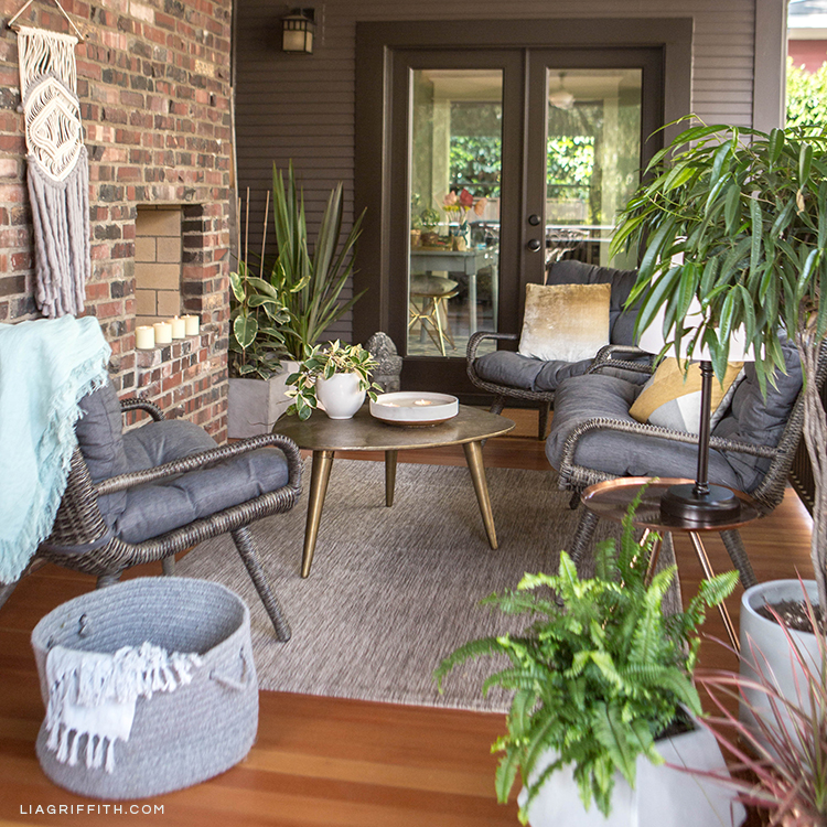 Cozy outdoor living space with Hayneedle wicker conversation set, cocktail table, indoor/outdoor rug, and geometric planters