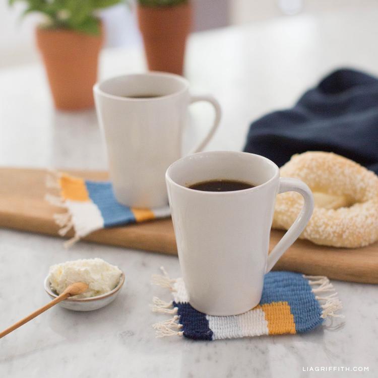 Kaffeetassen auf gesponnenen Untersetzern auf Küchentisch