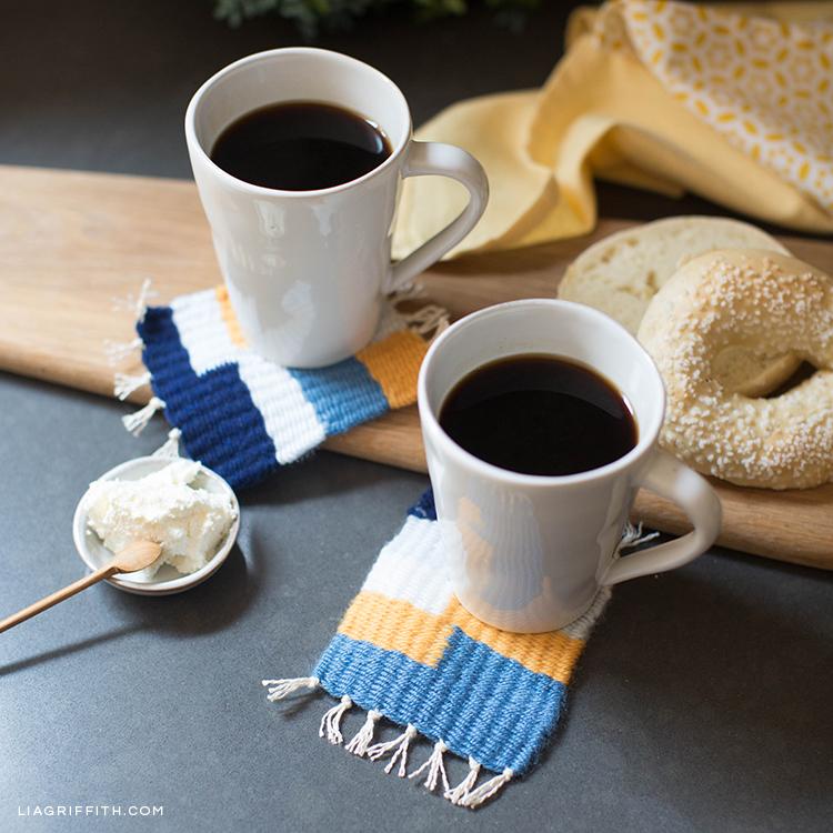 Kaffeetassen auf gewebten Untersetzern neben Bagel und Butter