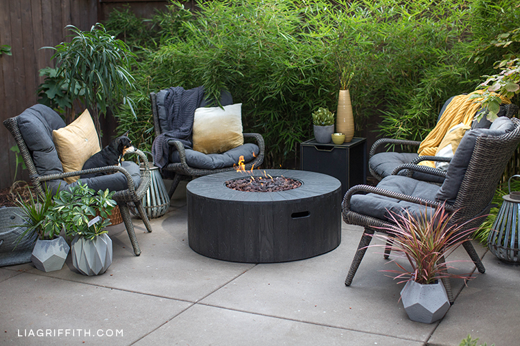 Outdoor fire pit from Hayneedle with wicker seating next to plants