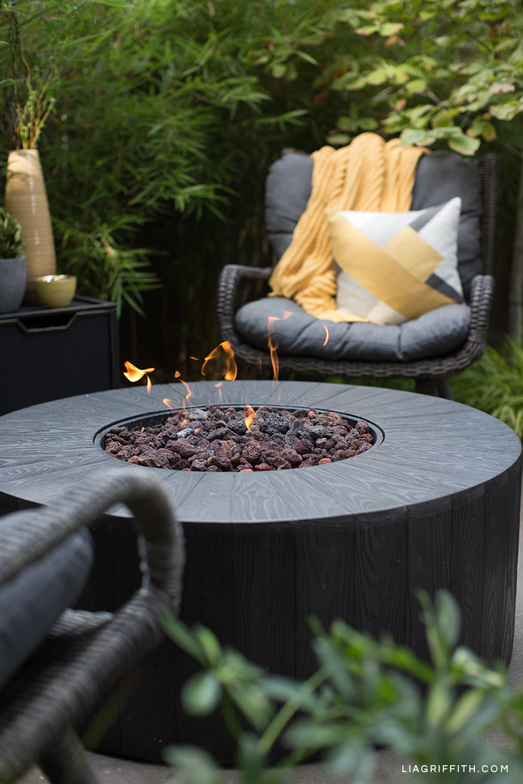 Outdoor fire pit from Hayneedle with blanket and pillow on wicker seat
