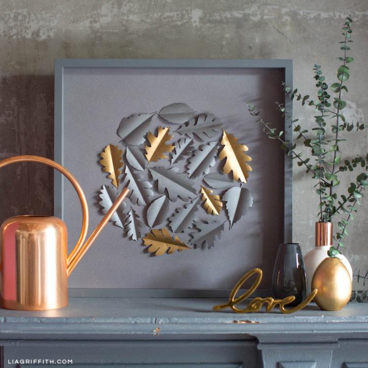 Papercut oak leaf framed art on mantle next to home decor
