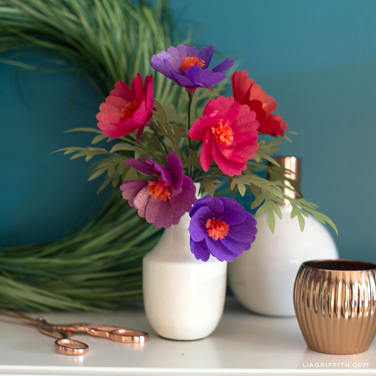 Tissue paper cosmos flowers in white vase in front of DIY wreath on table