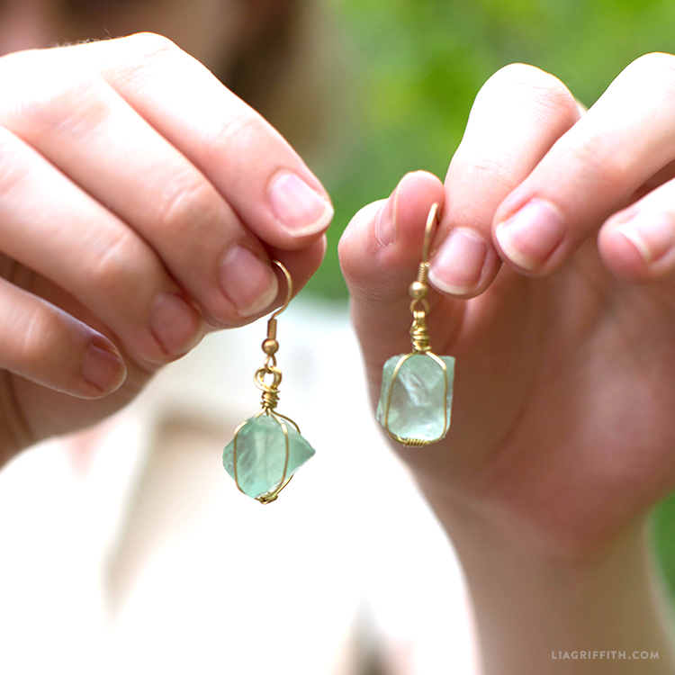 Designer's hands holding our wire wrapped earrings