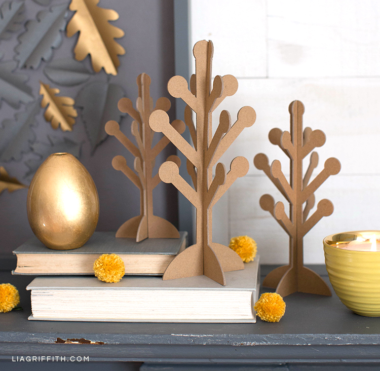 Scandinavian-style 3D paper trees on mantel with books, gold vase, pom pom billy balls, and paper oak leaf framed art