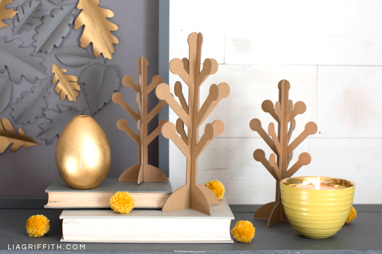 Scandinavian-style 3D paper trees on mantel with books, bowl, vase, billy balls, and paper oak leaf framed art