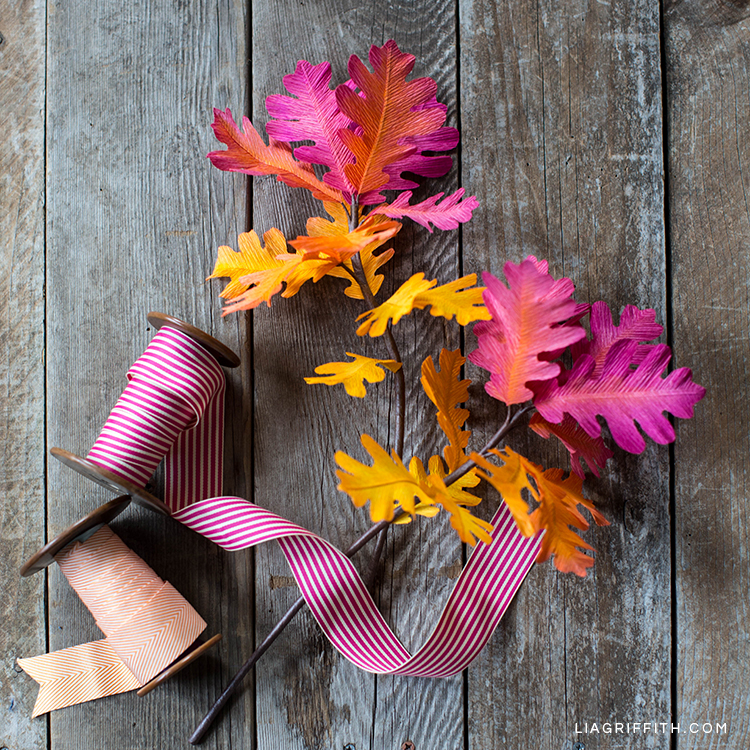 Pink, yellow, and orange ombré oak leaf branches on table next to ribbon