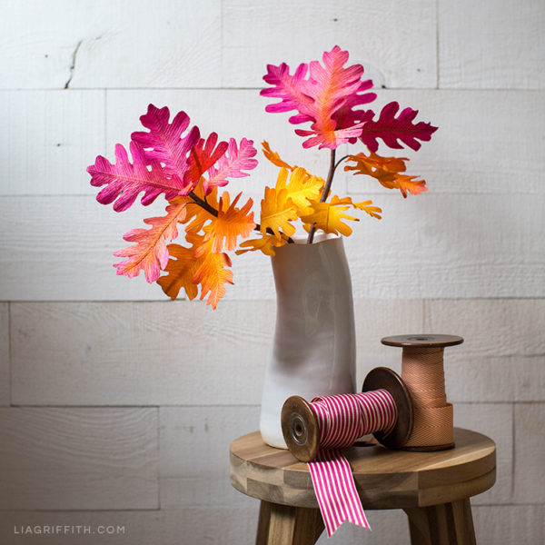 Ombré oak leaf branches in vase on stool next to ribbon