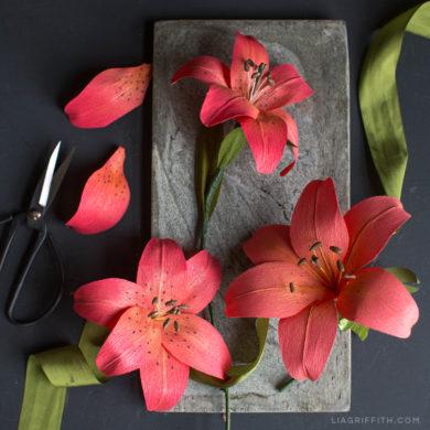 Red-orange crepe paper tiger lily next to scissors