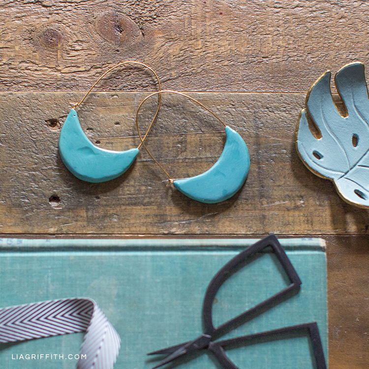 Turquoise polymer clay crescent hoop earrings on table