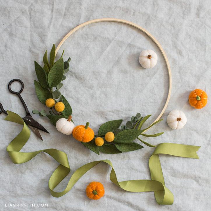 Felt pumpkin wreath with greenery next to scissors and ribbon