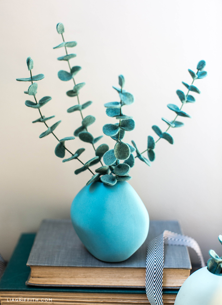 Baby blue eucalyptus in vase on book