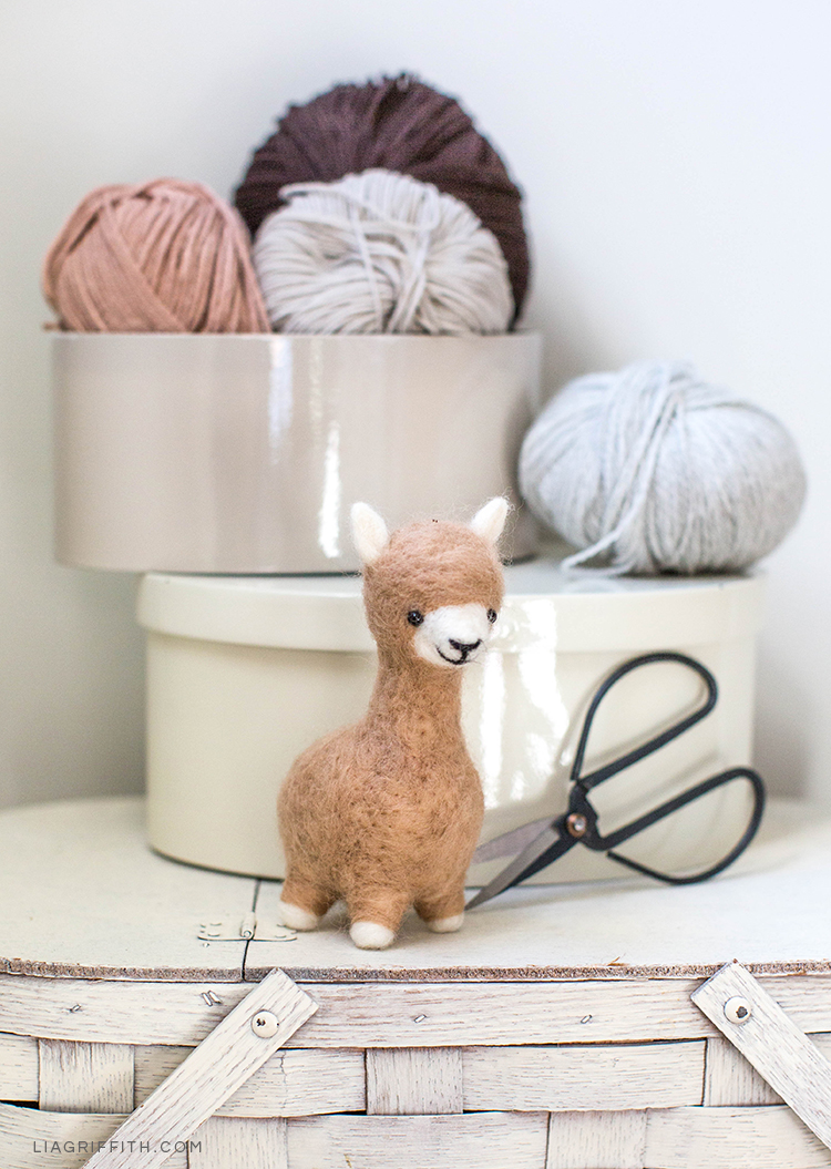 Needle felted alpaca next to scissors and yarn on basket