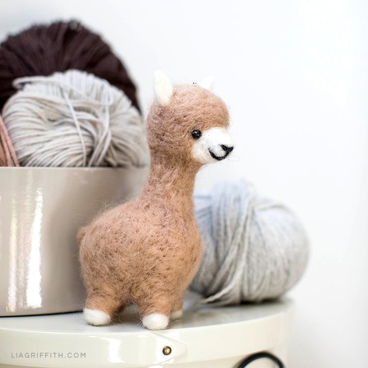 Needle felted alpaca sideways next to yarn