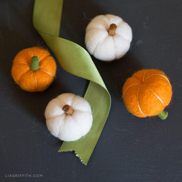 Mini felt pumpkins next to ribbon