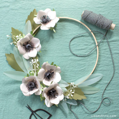 Black and white anemone flowers with seeded eucalyptus and leaves on a gold hoop