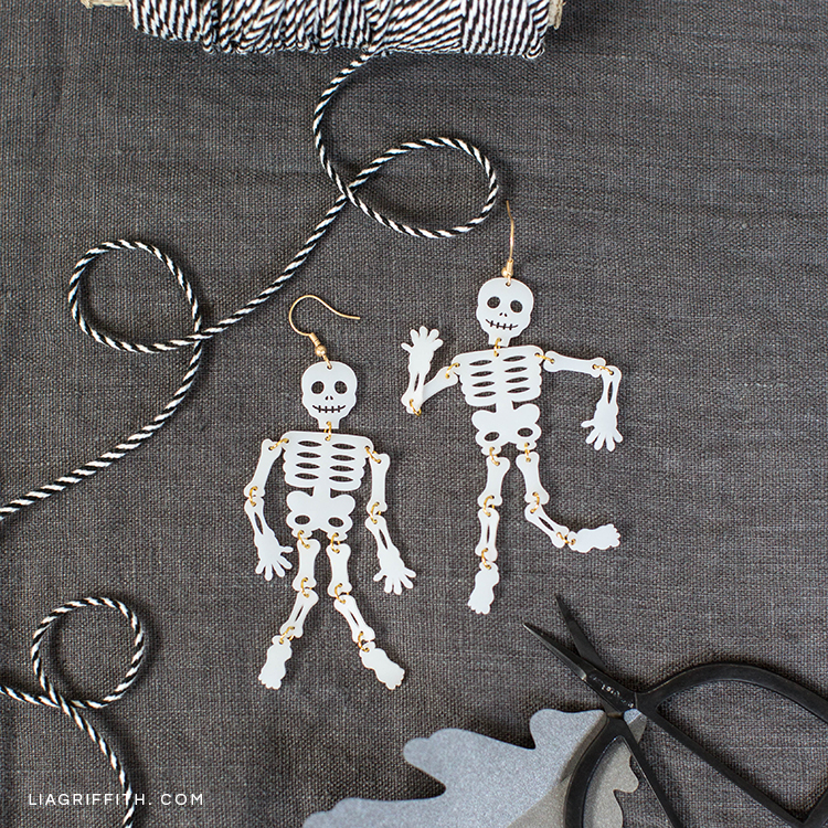 Shrink film skeleton earrings next to craft materials