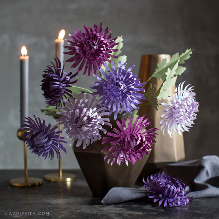 Purple paper spider chrysanthemums in vase next to candles on table