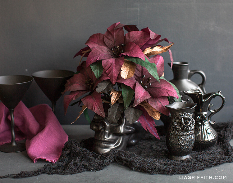 Crepe paper Queen of the Night lilies in black skull next to black pitchers and glasses
