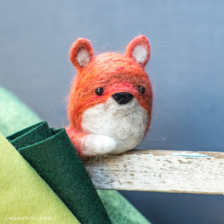 Needle felted fox next to felt