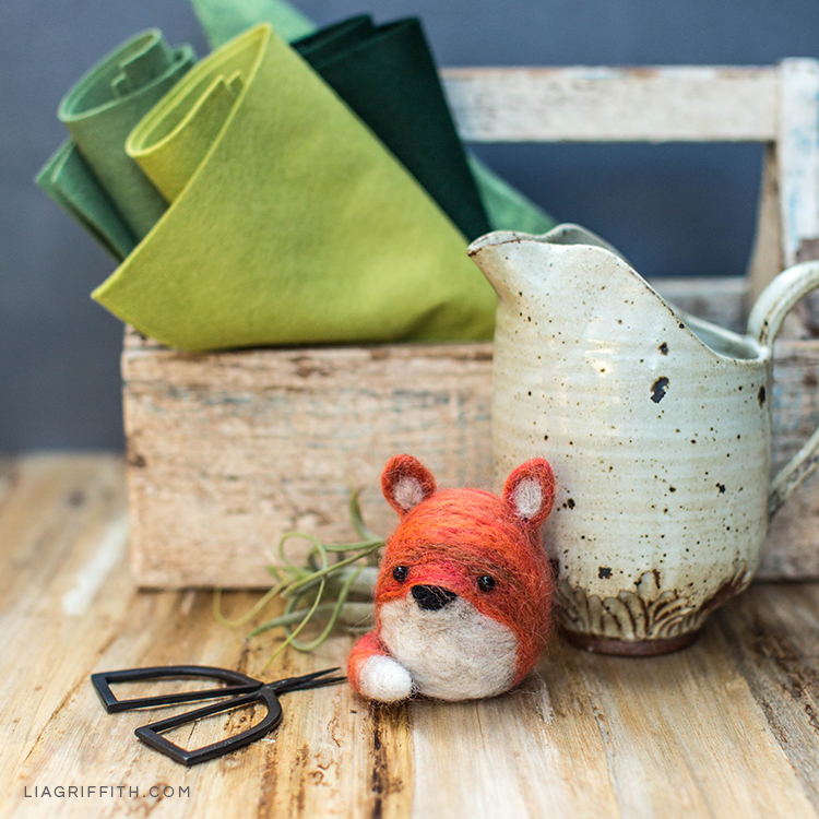 Needle felted fox on table next to scissors and felt