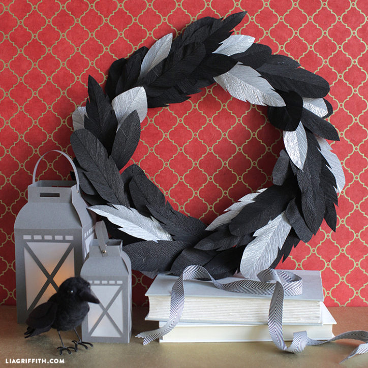 crepe paper crow feather wreath for Halloween next to lanterns and books