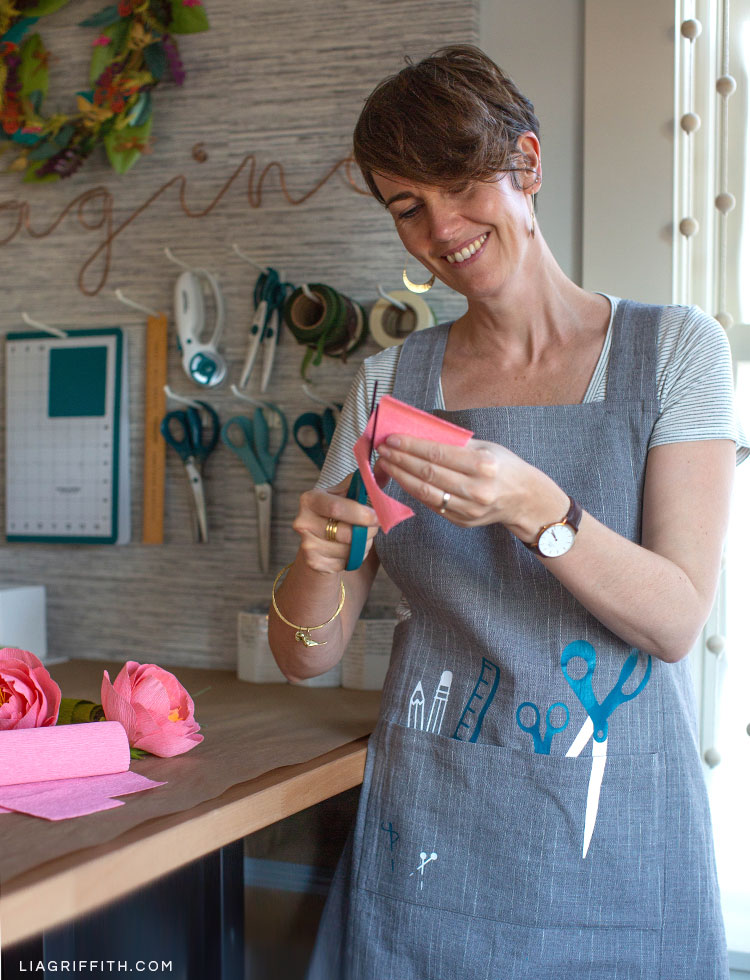 Woman cutting paper while wearing DIY craft apron in craft room