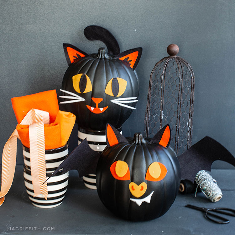 Felt pumpkin decorations for faux pumpkins next to craft tools and materials
