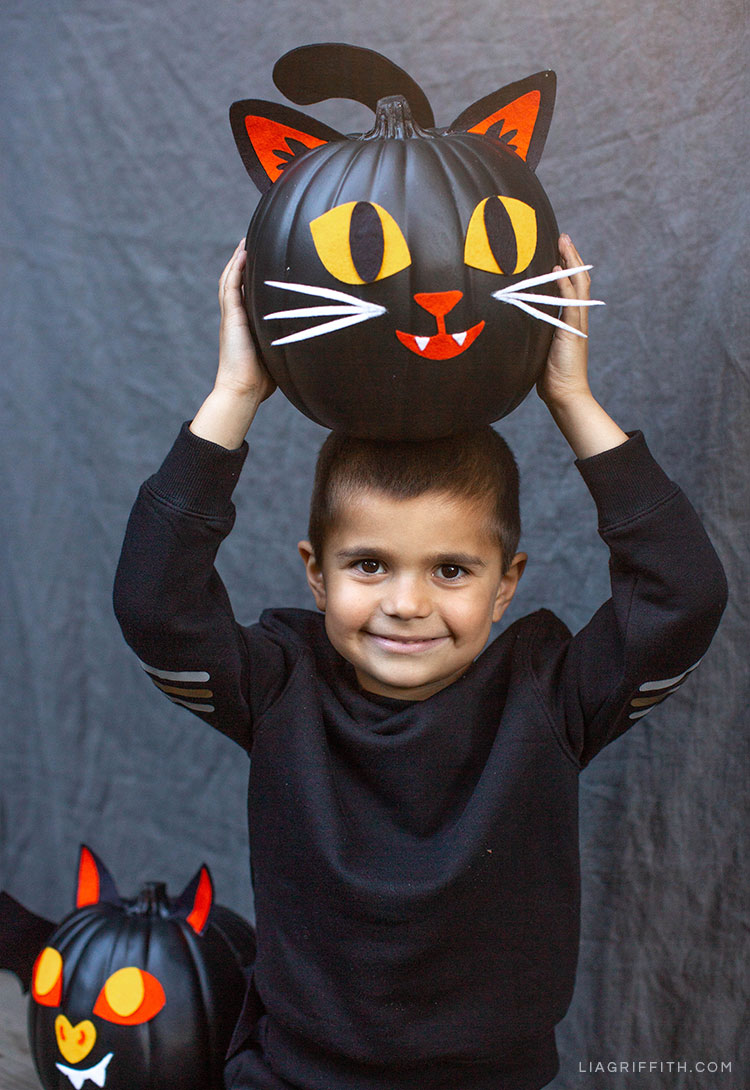 Boy holding felt cat pumpkin decoration